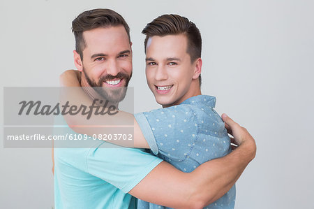 Happy homosexual couple looking at camera and hugging Stock Photo - Premium Royalty-Free, Image code: 6109-08203702
