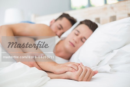 Homosexual couple sleeping on bed Stock Photo - Premium Royalty-Free, Image code: 6109-08203711