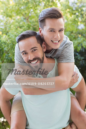 Man giving piggy back to his boyfriend Stock Photo - Premium Royalty-Free, Image code: 6109-08203727