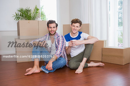 Happy homosexual couple holding mug and looking at camera Stock Photo - Premium Royalty-Free, Image code: 6109-08203762