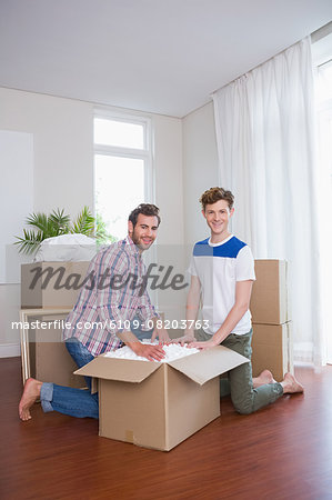 Happy homosexual couple unpacking box Stock Photo - Premium Royalty-Free, Image code: 6109-08203763