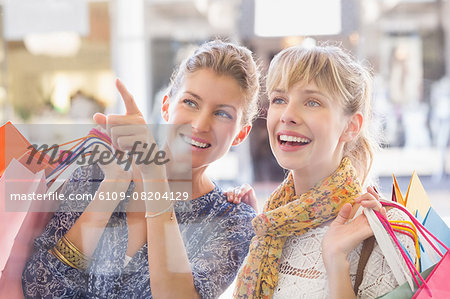 Beautiful women holding shopping bags looking at window Stock Photo - Premium Royalty-Free, Image code: 6109-08204129