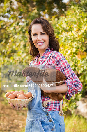 Happy brunette holding her chicken Stock Photo - Premium Royalty-Free, Image code: 6109-08204271