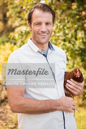 Happy farmer holding chicken Stock Photo - Premium Royalty-Free, Image code: 6109-08204273
