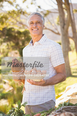 Happy farmer holding chicken and eggs Stock Photo - Premium Royalty-Free, Image code: 6109-08204288