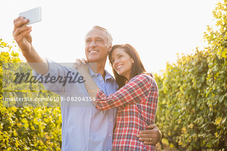 Happy couple embracing and taking selfies Stock Photo - Premium Royalty-Free, Image code: 6109-08204356