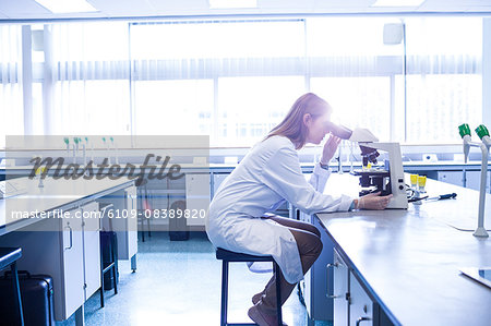Scientist working with a microscope in laboratory Stock Photo - Premium Royalty-Free, Image code: 6109-08389820