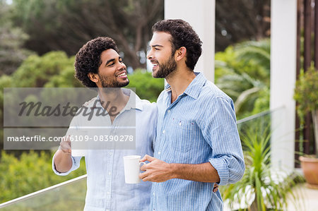 Smiling gay couple holding cups and talking Stock Photo - Premium Royalty-Free, Image code: 6109-08390278