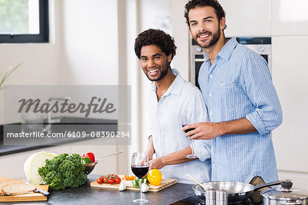 Happy gay couple drinking wine and cooking Stock Photo - Premium Royalty-Free, Image code: 6109-08390294