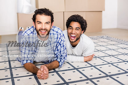 Happy gay couple laying on floor Stock Photo - Premium Royalty-Free, Image code: 6109-08390469