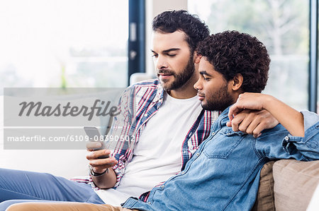 Happy gay couple using smartphone Stock Photo - Premium Royalty-Free, Image code: 6109-08390502