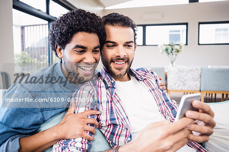 Happy gay couple using smartphone Stock Photo - Premium Royalty-Free, Image code: 6109-08390507