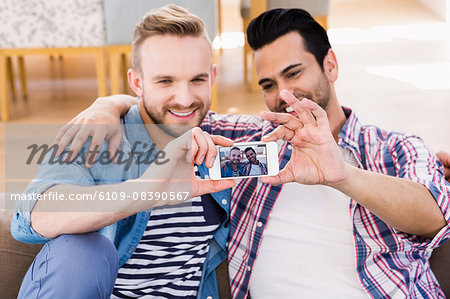 Gay couple relaxing on the couch taking selfie Stock Photo - Premium Royalty-Free, Image code: 6109-08390567