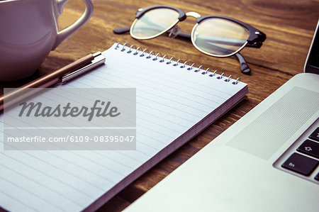 Notepad with laptops and eyeglasses on desk Stock Photo - Premium Royalty-Free, Image code: 6109-08395047