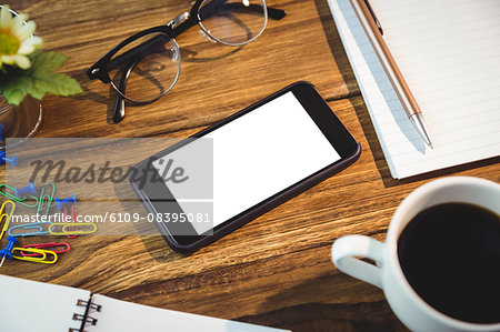 High angle view of office supplies and cellphone on table Stock Photo - Premium Royalty-Free, Image code: 6109-08395081