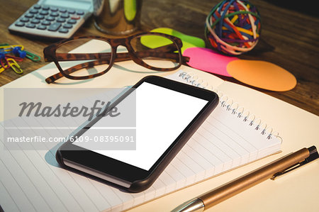 High angle view of mobile phone on notepad Stock Photo - Premium Royalty-Free, Image code: 6109-08395091