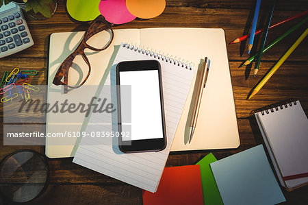 High angle view of mobile phone and office supplies Stock Photo - Premium Royalty-Free, Image code: 6109-08395092