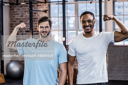 Two muscular men flexing biceps Stock Photo - Premium Royalty-Free, Image code: 6109-08397219
