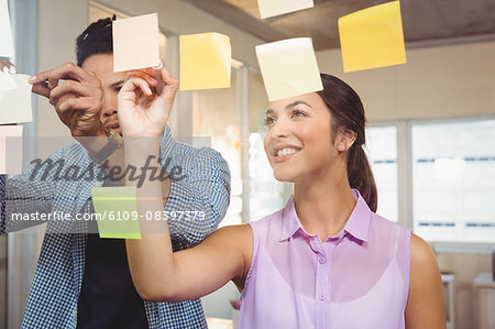 Business people smiling and working on sticky notes Stock Photo - Premium Royalty-Free, Image code: 6109-08397379