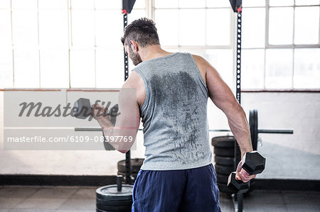 Fit man lifting heavy black dumbbells Stock Photo - Premium Royalty-Free, Image code: 6109-08397769