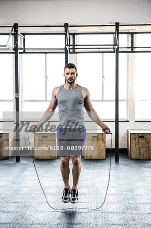 Fit man using skipping rope Stock Photo - Premium Royalty-Free, Image code: 6109-08397776
