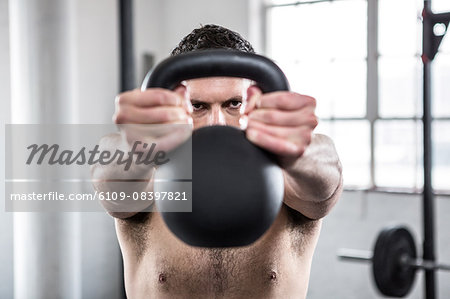 Fit shirtless man working out with kettlebell Stock Photo - Premium Royalty-Free, Image code: 6109-08397821