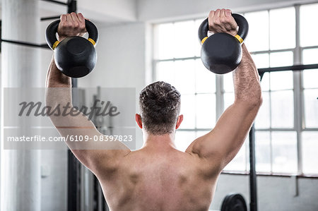 Fit shirtless man working out with kettlebells Stock Photo - Premium Royalty-Free, Image code: 6109-08397823
