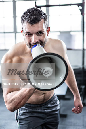 Fit shirtless man shouting with megaphone Stock Photo - Premium Royalty-Free, Image code: 6109-08397831