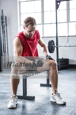 Fit man lifting heavy black dumbbell Stock Photo - Premium Royalty-Free, Image code: 6109-08397835