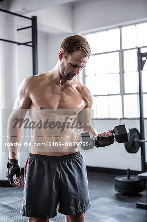 Fit man lifting heavy black dumbbell Stock Photo - Premium Royalty-Free, Image code: 6109-08397854