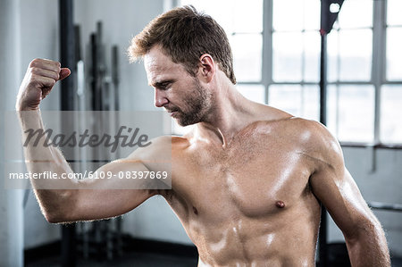 Fit man flexing his bicep Stock Photo - Premium Royalty-Free, Image code: 6109-08397869
