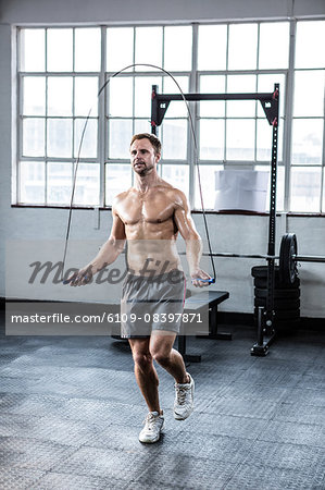 Fit man using skipping rope Stock Photo - Premium Royalty-Free, Image code: 6109-08397871