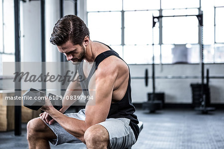 Fit man lifting heavy black dumbbell Stock Photo - Premium Royalty-Free, Image code: 6109-08397994