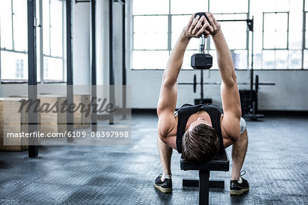Fit man lifting heavy black dumbbell Stock Photo - Premium Royalty-Free, Image code: 6109-08397998
