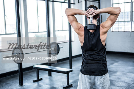 Fit man lifting heavy black dumbbell Stock Photo - Premium Royalty-Free, Image code: 6109-08398006