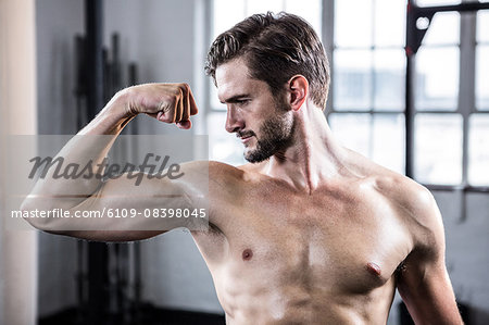 Fit shirtless man flexing his bicep Stock Photo - Premium Royalty-Free, Image code: 6109-08398045