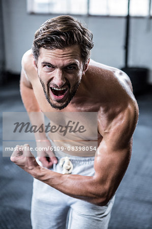 Fit shirtless man shouting and flexing Stock Photo - Premium Royalty-Free, Image code: 6109-08398054