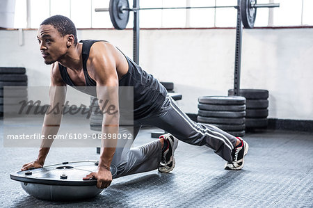 Fit man working out with bosu ball Stock Photo - Premium Royalty-Free, Image code: 6109-08398092