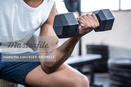 Fit man lifting heavy black dumbbells Stock Photo - Premium Royalty-Free, Image code: 6109-08398113