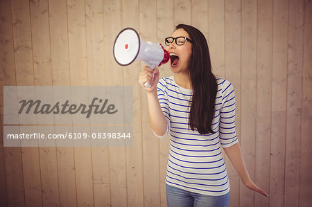 Beautiful woman shouting with megaphone Stock Photo - Premium Royalty-Free, Image code: 6109-08398344