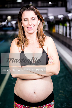Pregnant woman smiling crossed arms Stock Photo - Premium Royalty-Free, Image code: 6109-08398720