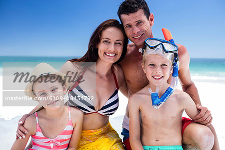 Cute family posing for camera with boy wearing snorkeling equipment on the beach Stock Photo - Premium Royalty-Free, Image code: 6109-08434792
