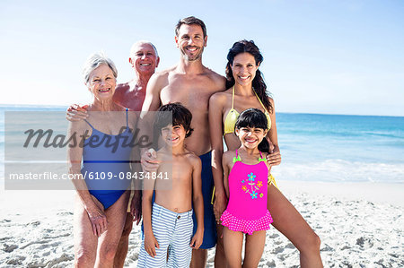 Cute family standing and smiling on the beach Stock Photo - Premium Royalty-Free, Image code: 6109-08434841