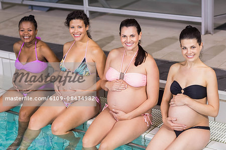 Smiling pregnant women touching their belly at the swimming pool Stock Photo - Premium Royalty-Free, Image code: 6109-08434982