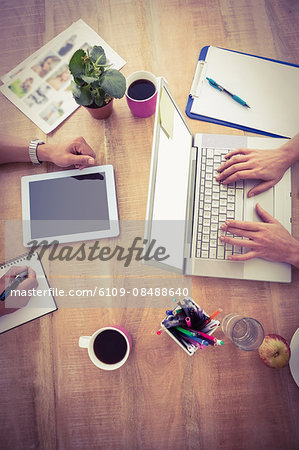 Colleagues using laptop and taking notes in the office Stock Photo - Premium Royalty-Free, Image code: 6109-08488640