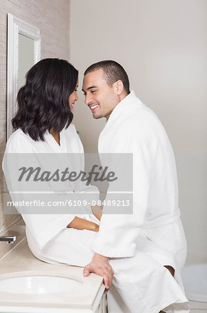 Smiling couple in bathrobe about to kiss in bathroom Stock Photo