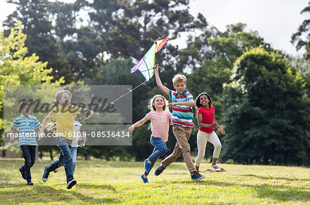 Happy children playing with a kite Stock Photo - Premium Royalty-Free, Image code: 6109-08536434