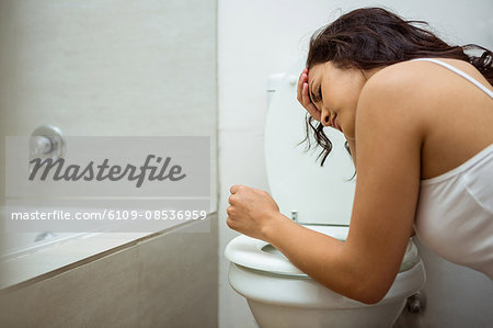 Young woman about to vomit into a commode toilet Stock Photo - Premium Royalty-Free, Image code: 6109-08536959