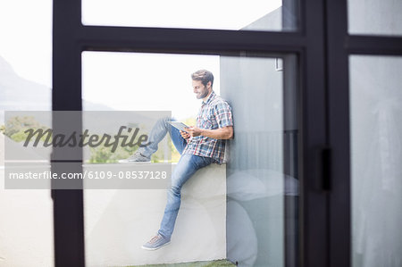 Man sitting on terrace using digital tablet Stock Photo - Premium Royalty-Free, Image code: 6109-08537128
