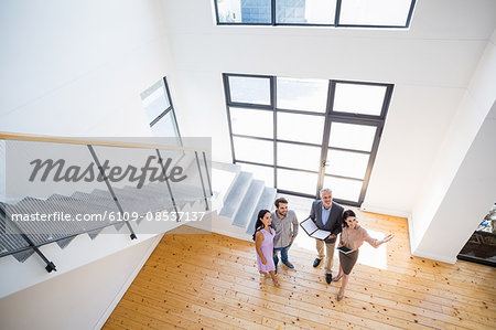 Real estate agent showing new house to couple Stock Photo - Premium Royalty-Free, Image code: 6109-08537137